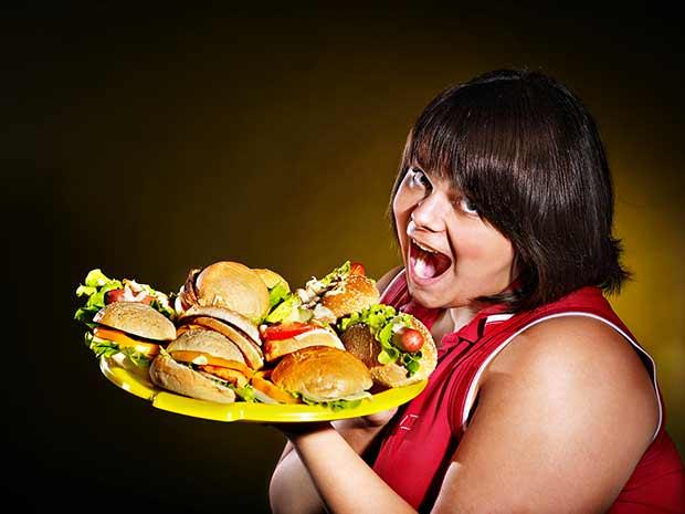 bigstock-Overweight-woman-holding-hambu-53097661
