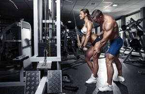 beautiful young sporty sexy couple doing triceps workout in gym