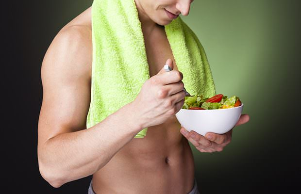 Fitness man holding a bowl of fresh salad on dark background